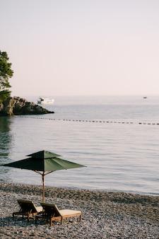 Роскошные деревянные шезлонги и зеленые пляжные зонтики на песчаном пляже