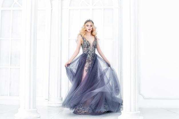 シックなロングドレスとインテリアの王冠の豪華な若い美しいモデルのブロンドの女性