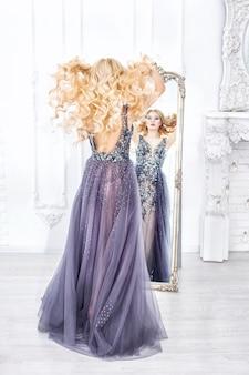インテリアのシックなロングドレスで豪華な若い美しいモデルのブロンドの女性