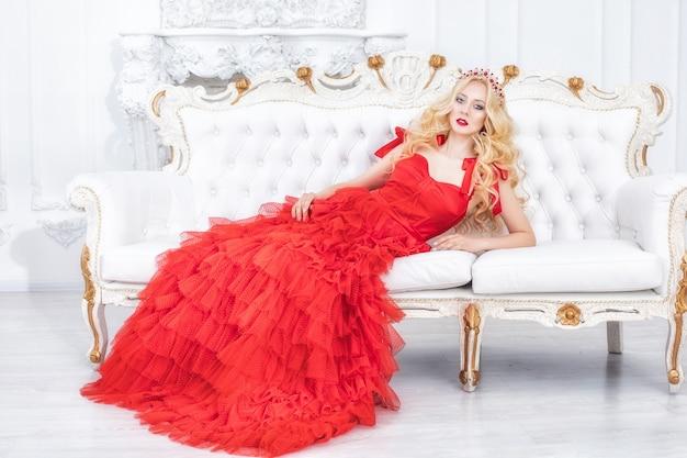シックな赤いドレスとインテリアの装飾で豪華な若い美しいモデルのブロンドの女性