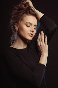 눈을 감고 스튜디오에서 포즈를 취하는 검은 드레스를 입은 고급스러운 젊은 모델