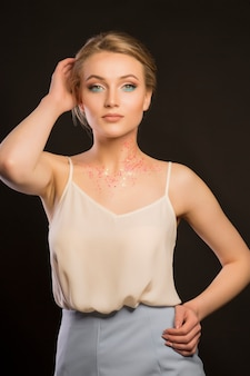 暗いスタジオで彼女の首にキラキラと豪華な若いモデル