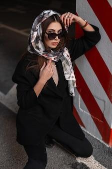 スタイリッシュな黒のコートを着た頭にシルクのエレガントなスカーフをかけたサングラスをかけた豪華な若い女性が、駐車場の赤白の縞模様の柱の近くのアスファルトで休んでいます。魅力的なビジネスガールのファッションモデル。