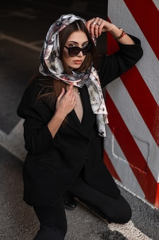 Luxurious young woman in sunglasses in silk elegant scarf on head in stylish black coat is resting on the asphalt near red-white striped column in the parking. attractive business girl fashion model.
