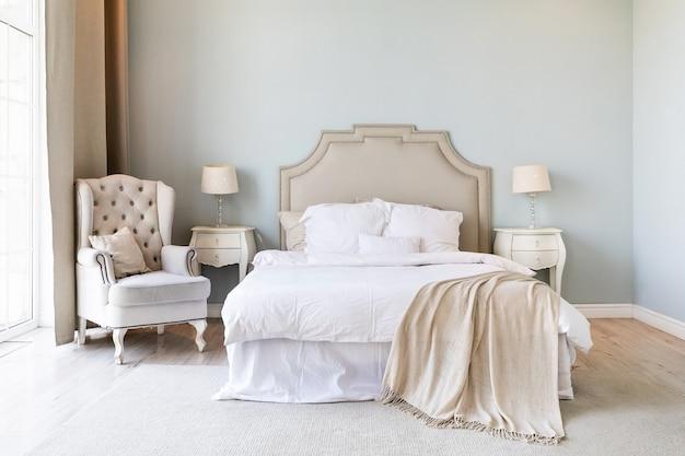 Роскошная квартира-спальня с мебелью в классическом стиле. интерьер с большой двуспальной кроватью и двумя прикроватными тумбочками.