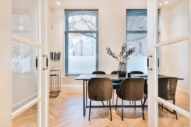 오픈 플랜 하우스의 흰색 주방을 배경으로 한 쪽모이 세공 마루와 검은 색 식당이있는 고급 아파트 식당