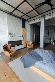 어두운 색상의 로프트 스타일의 고급 아파트입니다. 벽난로가있는 세련되고 현대적인 침실