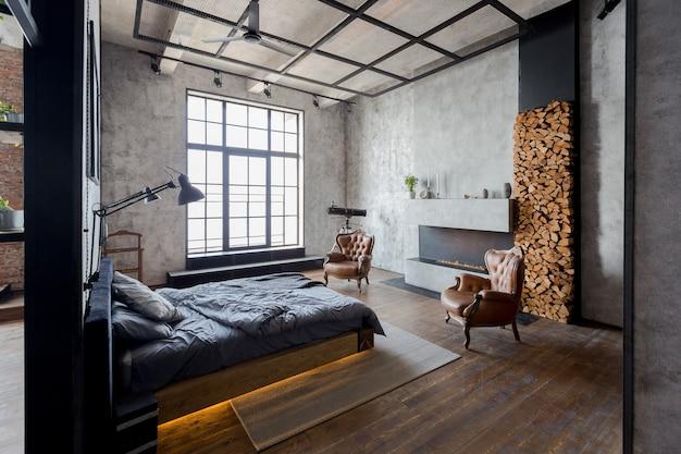 어두운 색상의 로프트 스타일의 고급 아파트입니다. 벽난로가있는 세련되고 현대적인 아늑한 침실 공간