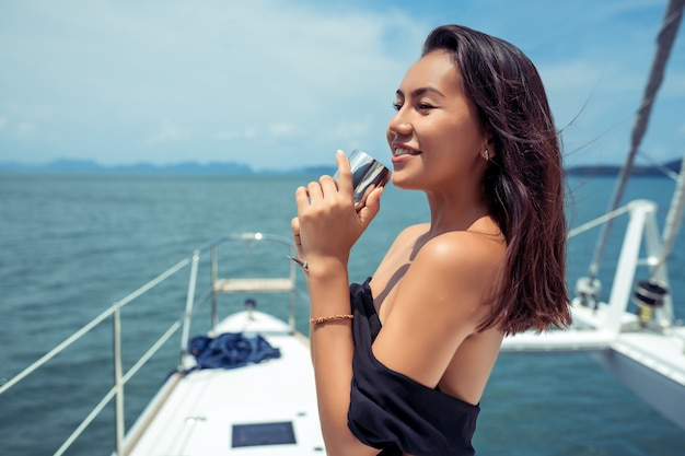 Luxury asian woman in evening black dress drinking champagne on the deck of a yachts