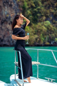 Роскошная азиатка в вечернем черном платье пьет шампанское на палубе яхты