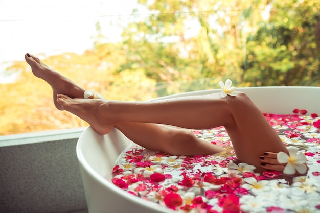 Luxury bath tub in spa with woman's bare legs showing through.
