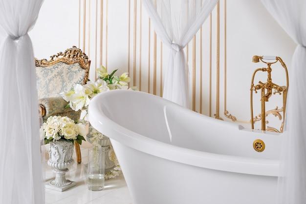 황금 가구 세부 사항 및 캐노피와 밝은 색상의 고급 욕실. 우아한 클래식 인테리어.