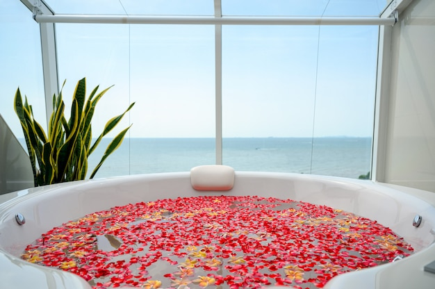 Luxury bathtub with colorful flower in water with sea view