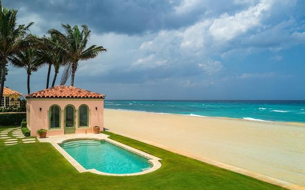 古いデザインの休暇のホームの空の芝生の床のデッキの近くの豪華なビーチハウスと海の見えるスイミングプール...