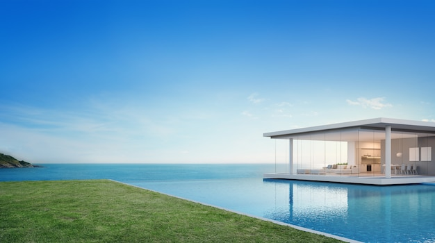Luxury beach house and sea view swimming pool near empty grass floor deck in modern design.