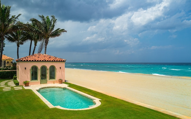 Luxury beach house and sea view swimming pool near empty grass floor deck in old design vacation hom...