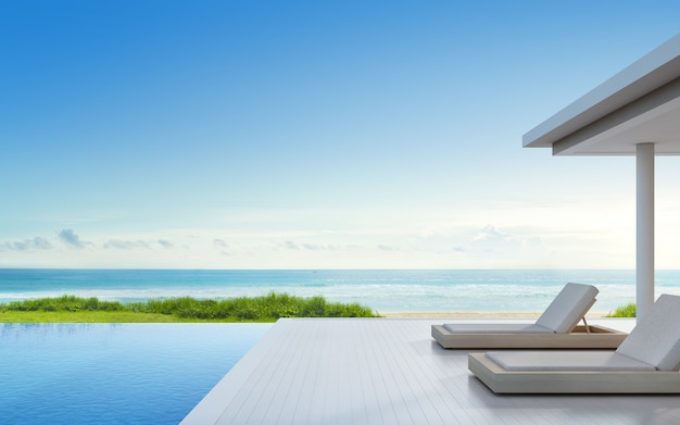 Роскошный пляжный дом с бассейном с видом на море и террасой в современном дизайне. Premium Фотографии