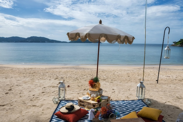 Luxury beach picnic set with snack fruit champagne decorated flowers in hotel resort