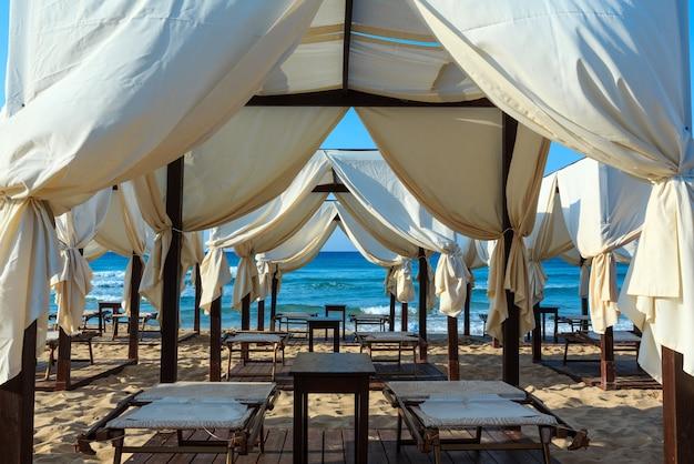 Роскошные пляжные палатки с навесами на утреннем райском белом песчаном пляже (песколузе, саленто, апулия, юг италии). самый красивый морской песчаный пляж апулии.