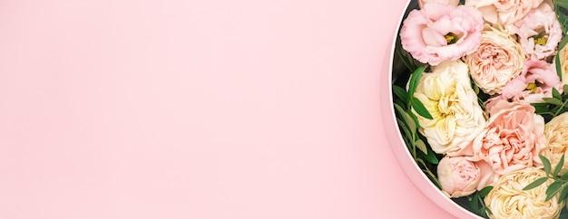 Роскошные красивые цветы в шляпе круглой коробке на розовом фоне с копией пространства. подарок или подарок
