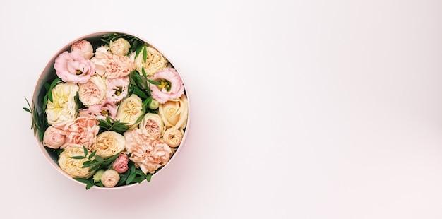 Роскошные красивые цветы в шляпе круглой коробке на розовом фоне с копией пространства. подарок или подарок Premium Фотографии