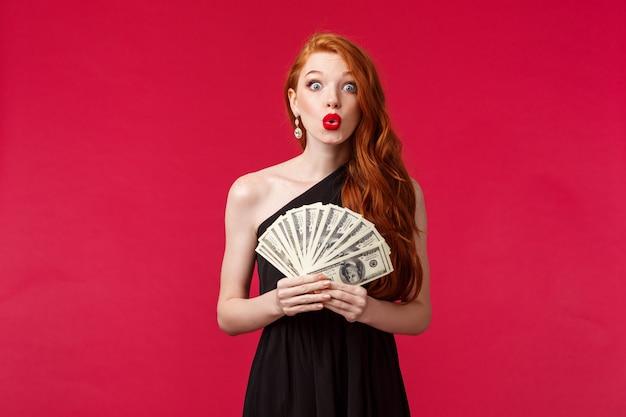 럭셔리, 아름다움과 돈 개념입니다. 검은 세련된 드레스 입술을 접고 현금으로이기는 놀란 찾고 바보 같은 잘 생긴 젊은 빨간 머리 여자는 상금을 받고, 붉은 벽에 서서