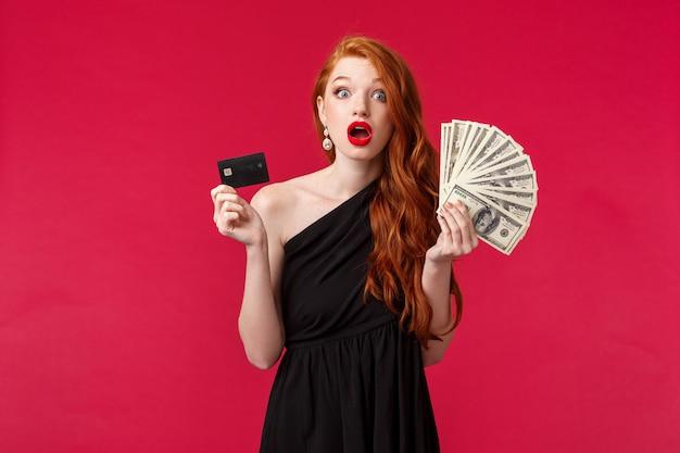 贅沢、美しさとお金の概念。驚きの愚かな若い魅力的な女性は突然金持ちになり、賞金を獲得し、ドルとクレジットカードを保持し、あえぎ、不信感を見つめ、赤い壁