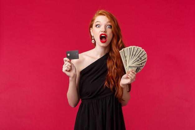 럭셔리, 아름다움과 돈 개념입니다. 상금, 수천 달러를 받고, 현금과 신용 카드의 팬을 잡고, 놀랍게도, 붉은 벽으로 행운과 놀라는 소녀 표현 불신의 초상
