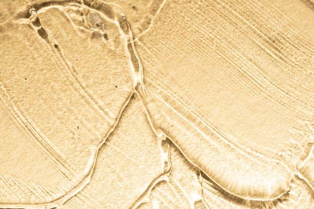 Деталь текстуры роскошной косметической сыворотки на золотом металлическом фоне