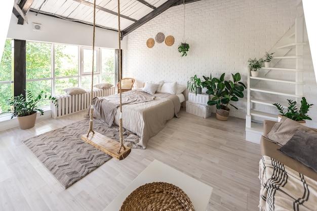 ミニマリストスタイルの素朴なコテージの豪華なベッドルームのデザイン。白い壁、パノラマの窓、天井の装飾の木製要素、広々とした部屋の真ん中でロープスイング。