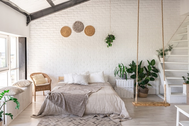 미니멀 스타일의 소박한 별장에 고급 침실 디자인. 흰 벽, 탁 트인 창문, 천장 장식의 목재 요소, 넓은 방 한가운데에 로프 스윙.