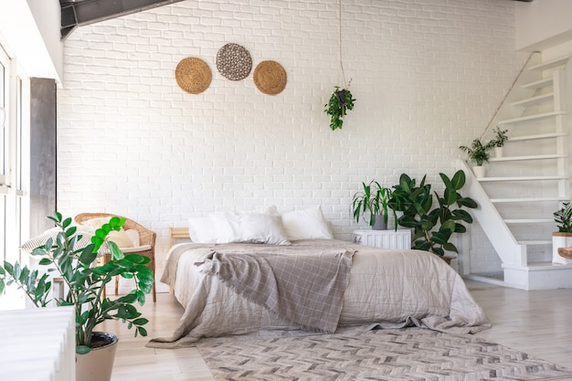 Luxury bedroom design in a rustic cottage in a minimalist style. white walls, panoramic windows, wooden elements of decoration on the ceiling, rope swings in the middle of a spacious room.