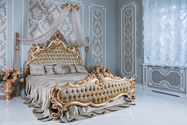 Роскошная спальня в светлых тонах с золотыми деталями мебели. большая удобная двуспальная королевская кровать в элегантном классическом интерьере