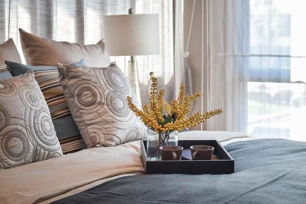 Luxury bedroom interior design with decorative tea set and striped pillows on bed