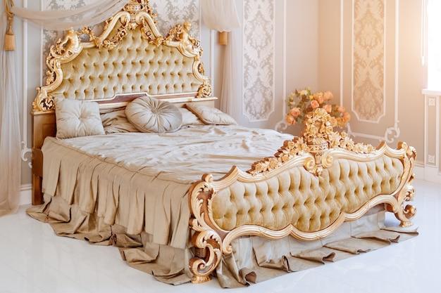 Luxury bedroom in light colors with golden furniture details
