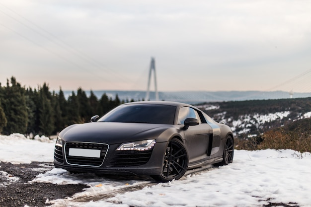 A luxury black sport coupe parking on the snowy road in the forest.