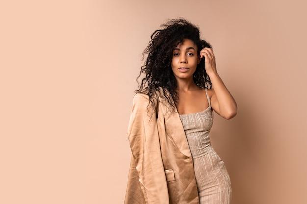 황금 빛나는 드레스 포즈에 아름 다운 물결 모양의 머리카락과 함께 럭셔리 흑인 여성. 파티 분위기.