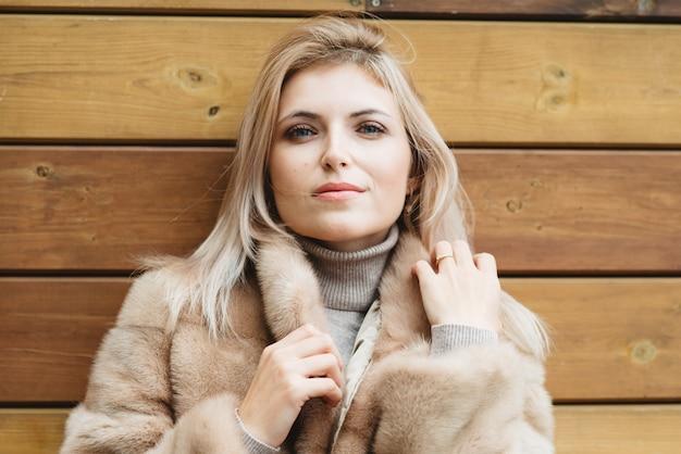 木の壁に30歳の毛皮のコートで青い目と長い髪の豪華なブロンドの女性。