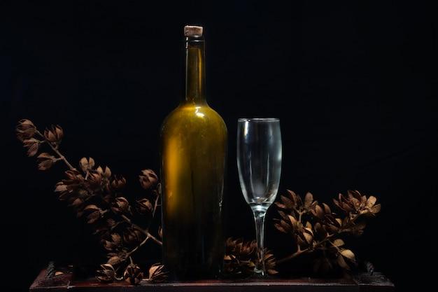 고급 병 와인과 검은 배경에 마른 꽃