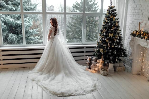 大きなパノラマの窓の近くのクリスマスのウェディングドレスの豪華な花嫁。クリスマスのウェディングドレスの豪華な花嫁。