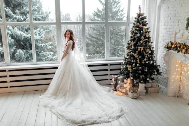 クリスマスツリーの近くのウェディングドレスの豪華な花嫁