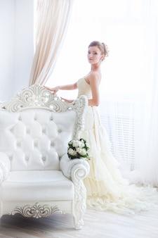 Роскошной невесте стоит наряжаться у окна на светлом фоне.