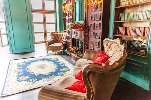 홈 라이브러리의 럭셔리 클래식 인테리어. 책장, 책, 안락 의자, 소파 및 벽난로가있는 거실. 우아한 가구로 깨끗하고 현대적인 장식. 교육은 연구 지혜 개념을 읽습니다.
