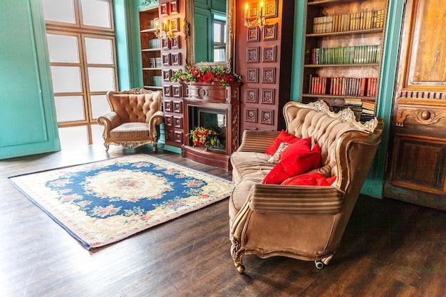 가정 도서관의 럭셔리 클래식 인테리어 책장, 책, 안락 의자, 소파 및 벽난로가있는 거실 프리미엄 사진