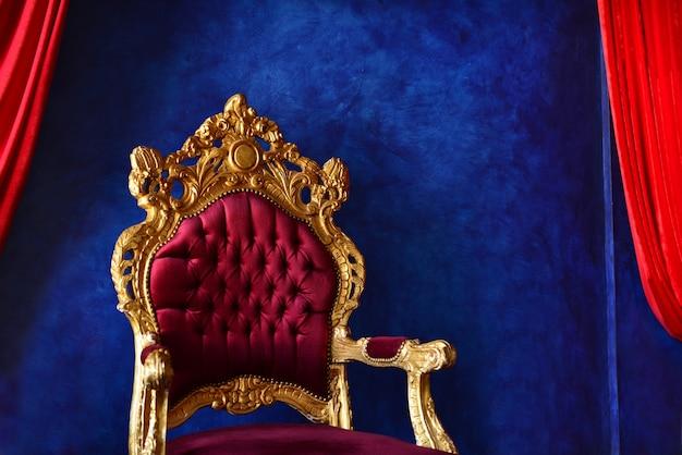 Роскошный классический интерьер с синей стеной и пурпурно-золотым креслом. необыкновенный синий и фиолетовый интерьер. синий и красный контраст со стенами. дорогой домашний интерьер с фиолетовым креслом.
