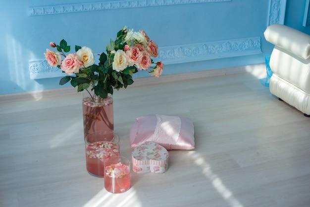 Роскошный чистый ярко-белый салон. просторная комната с солнечным светом и цветами в вазах, с декоративным камином, милыми розовыми пледами и вазой с зефиром. идея и концепция девичьей комнаты