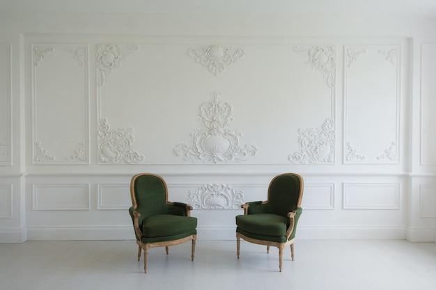 Роскошный чистый ярко-белый интерьер со старинными старинными зелеными стульями над дизайном стены барельеф лепнина лепные элементы рококо