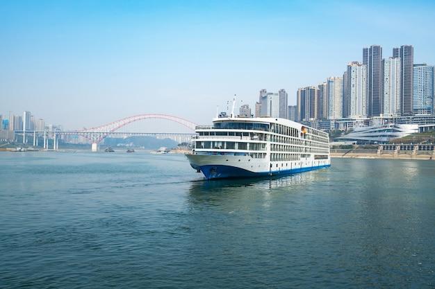 Luxury cruise ships sailing on the yangtze river, the city skyline in chongqing, china