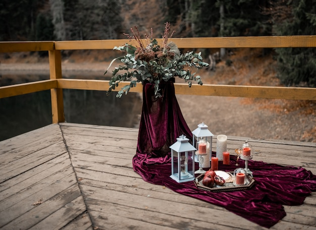 Luxury decorated table with burgundy color and candles for a romantic date.