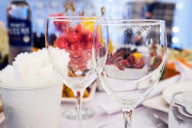 레스토랑에서 고급스러운 우아한 테이블 세팅 저녁 식사. 축제 아름답게 장식된 웨딩 테이블에 있는 유리잔. 레스토랑 테이블에 세련된 와인잔. 결혼식 하객을 위해 테이블이 제공됩니다.